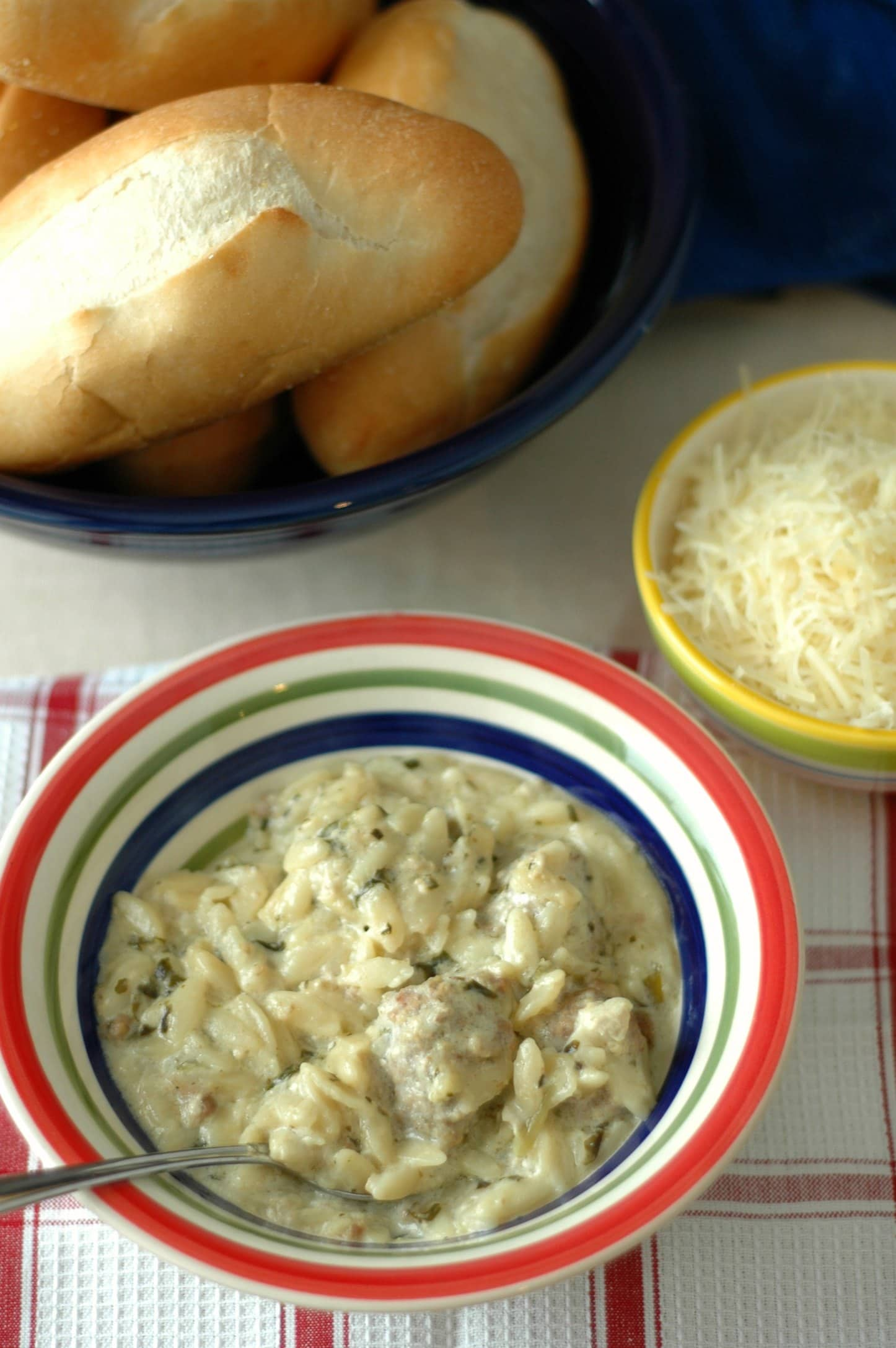 White bowl with colored rim of Creamy Meatball and Orzo Soup, baked roll and shredded cheese