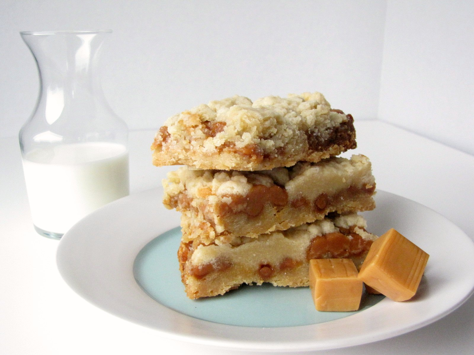 Slow Cooker Salted Caramel Cookie Bars on a plate with caramels and milk