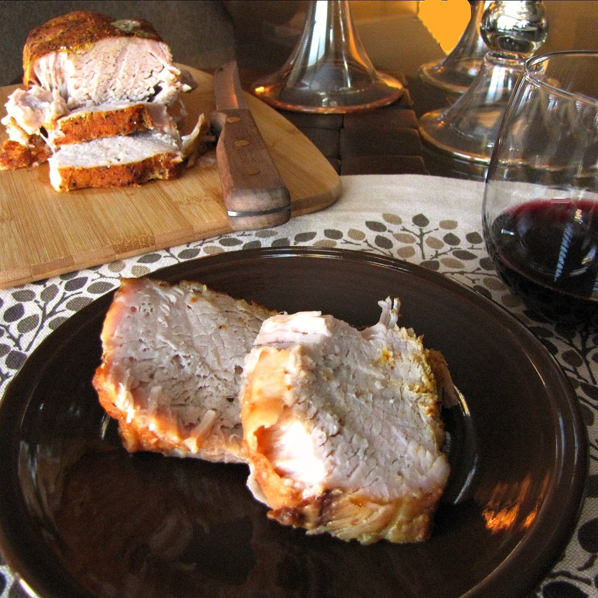 Two sliced pieces of Sweet and Spicy Pork Roast on a brown plate with a glass of red wine