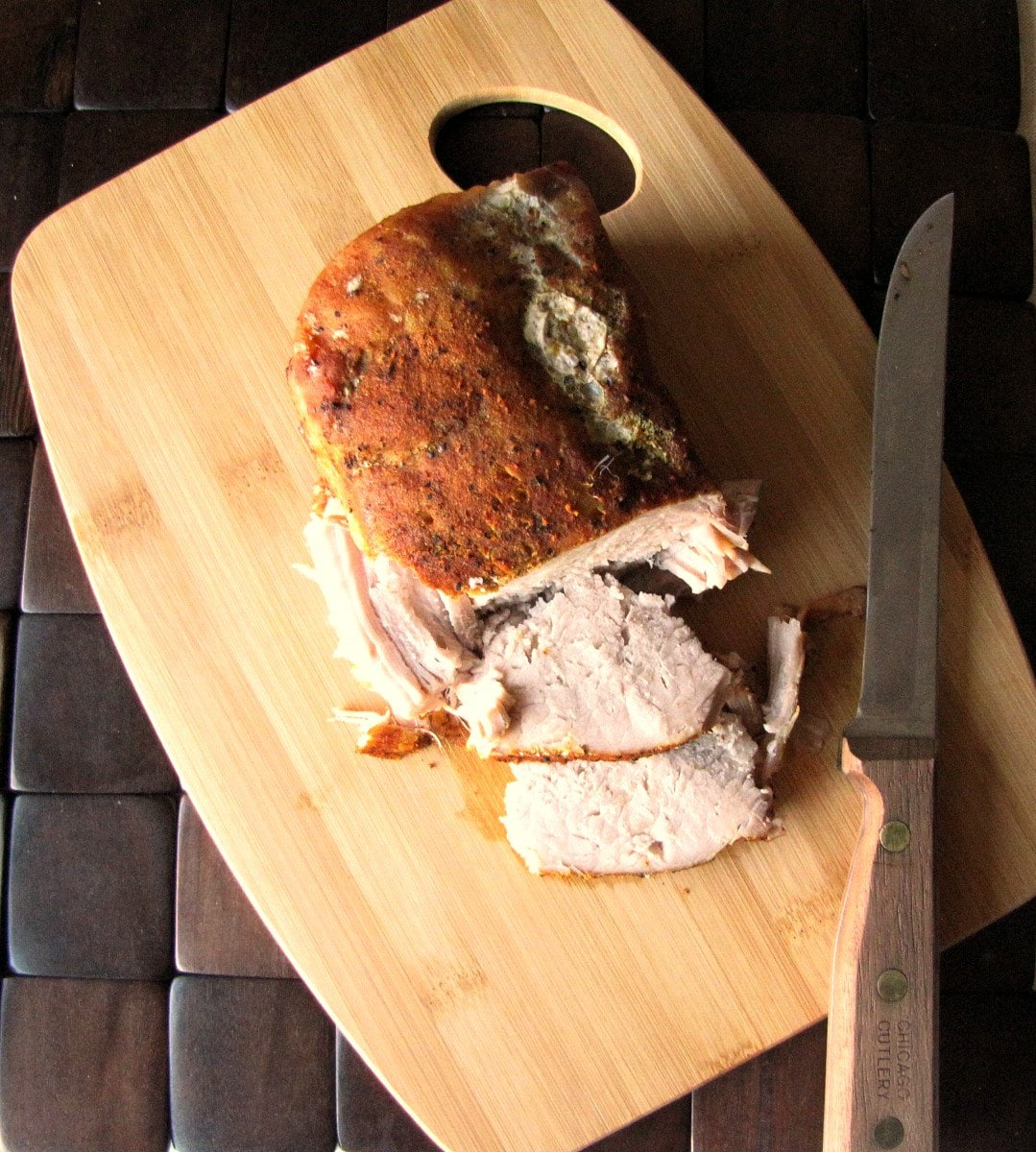 pork roast on carving board, knife and two slices
