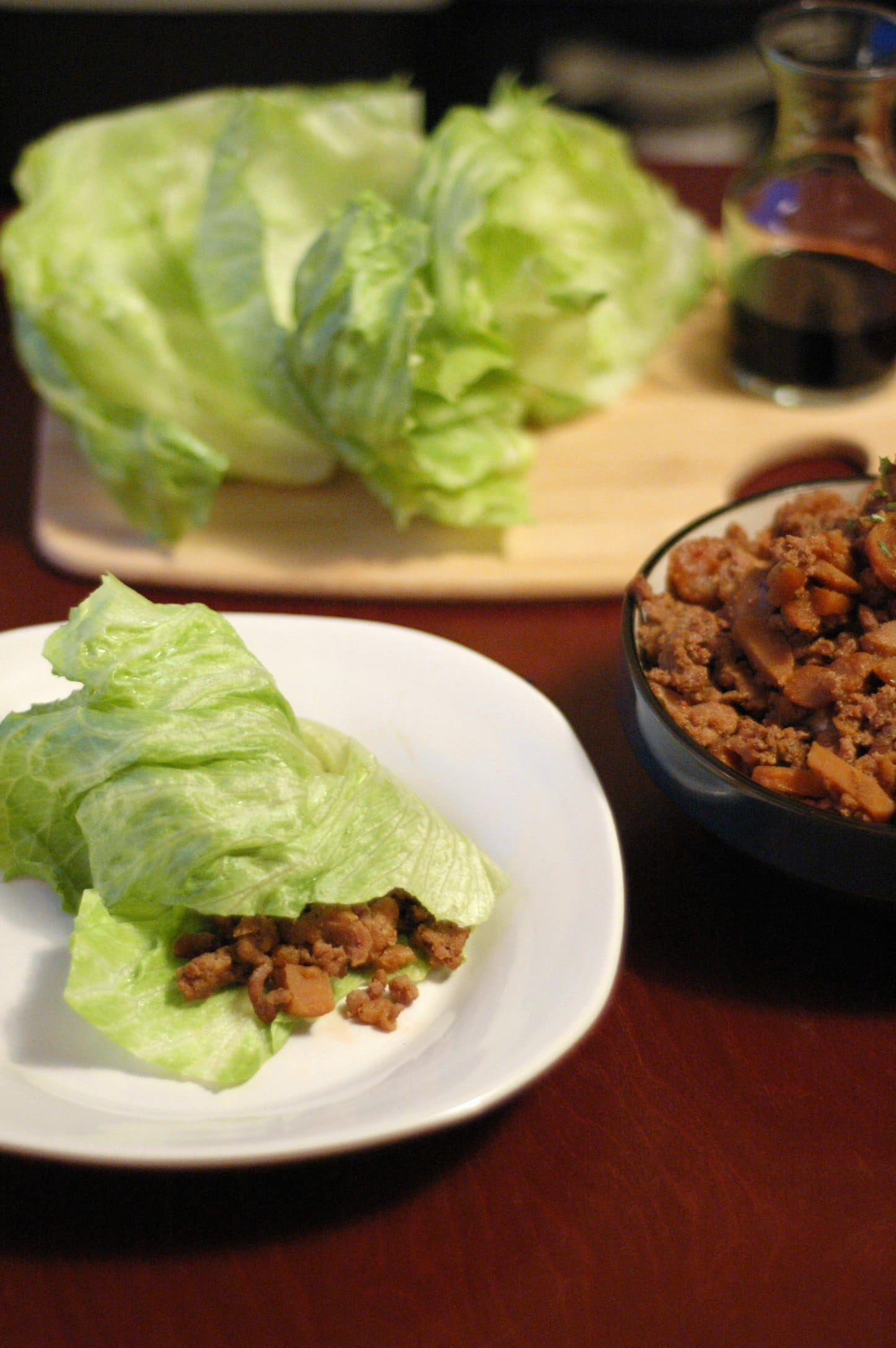 lettuce wrap on white plate, head of lettuce on cutting board and black bowl with pork mixture in background