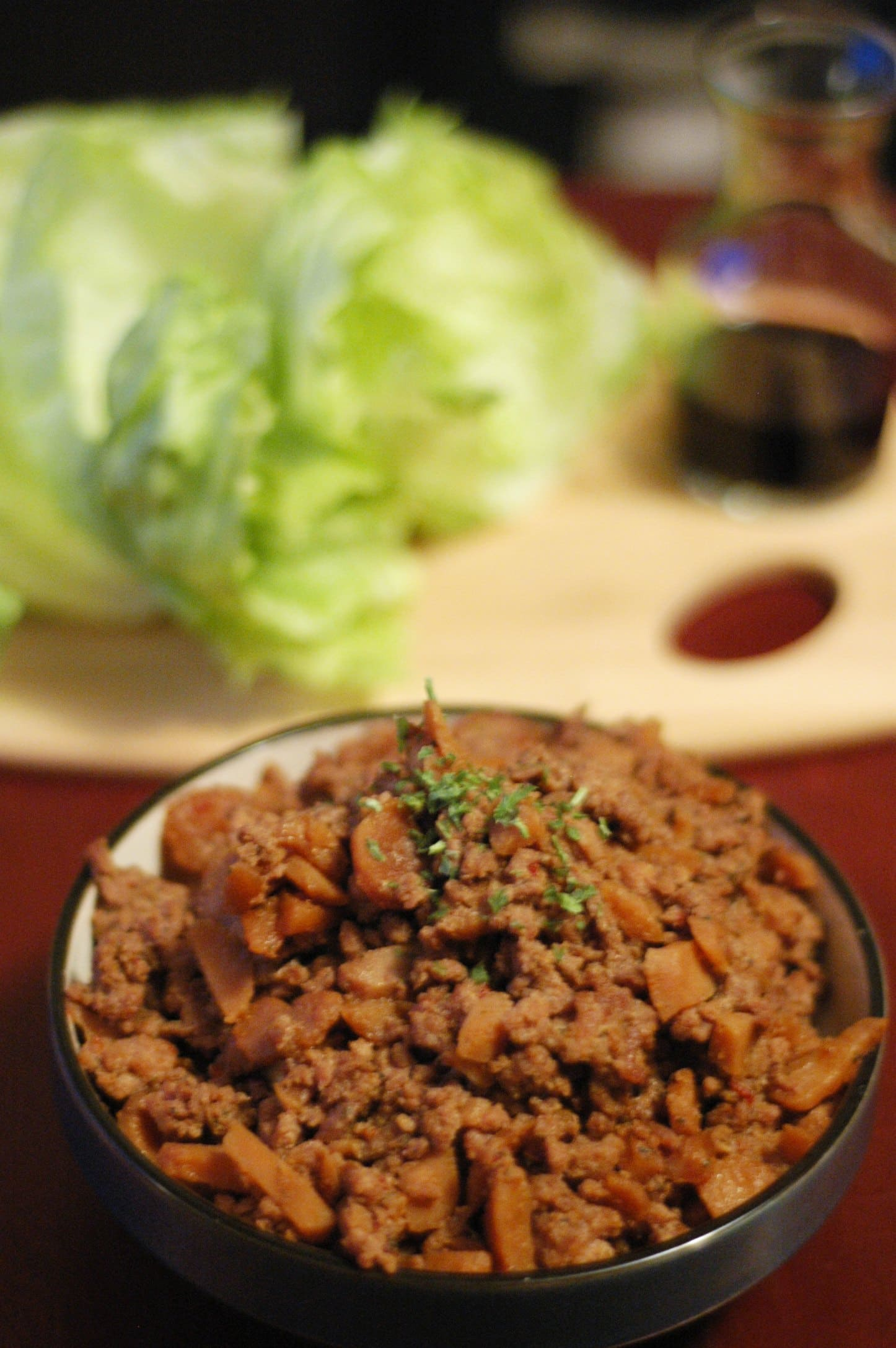 Black bowl with pork mixture with head of lettuce on cutting board in background
