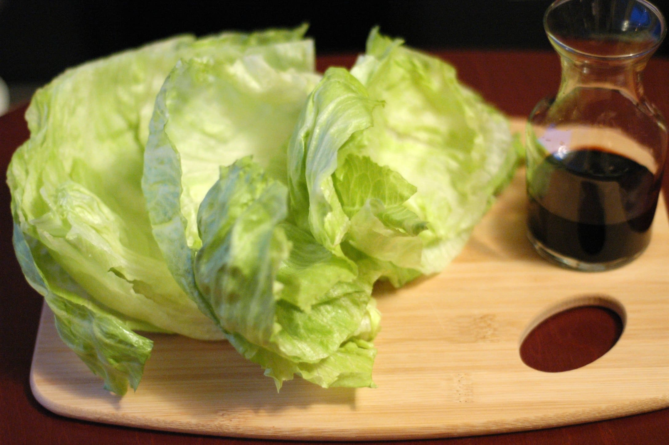 Head of lettuce on cutting board with cruet of soy sauce