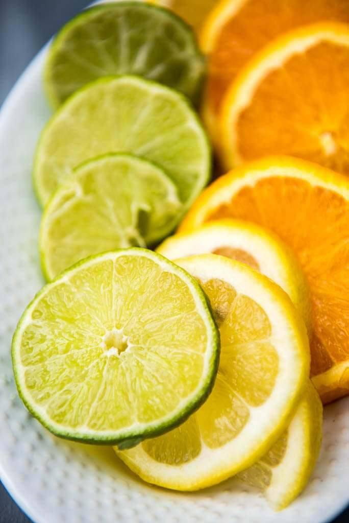 Close up shot of lemon and lime slices on a white platter.