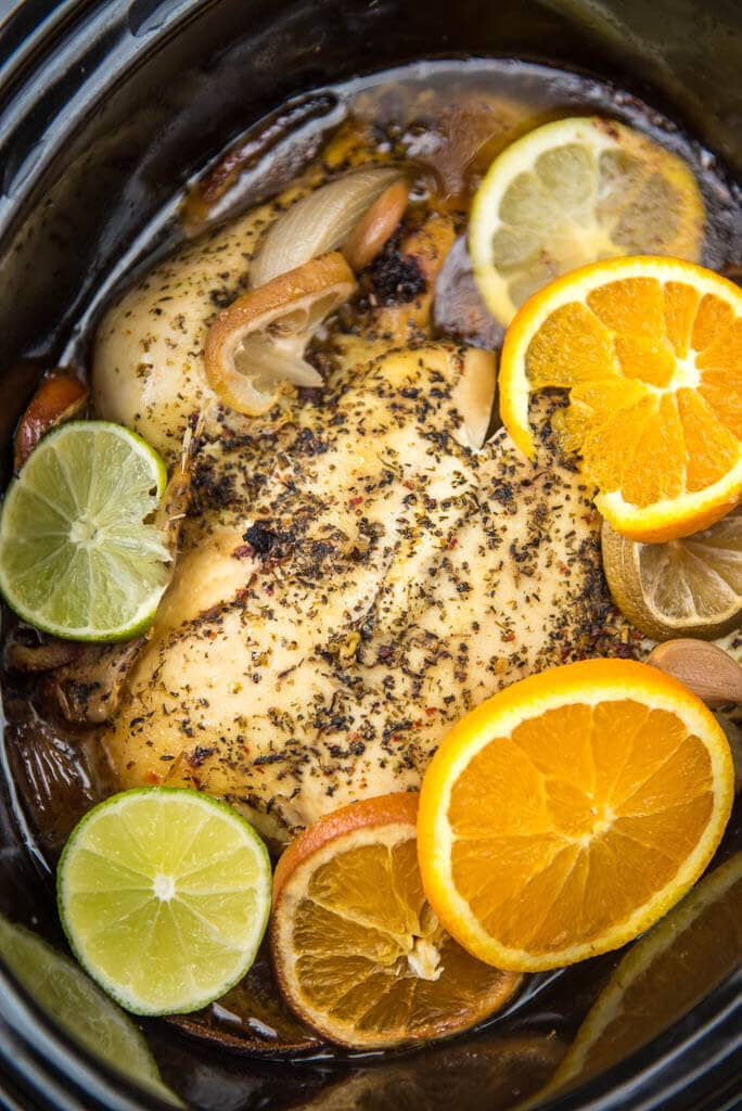 Cooked slow cooker whole chicken in black slow cooker covered in herbs with lemon and lime slices, onion and garlic surrounding it.