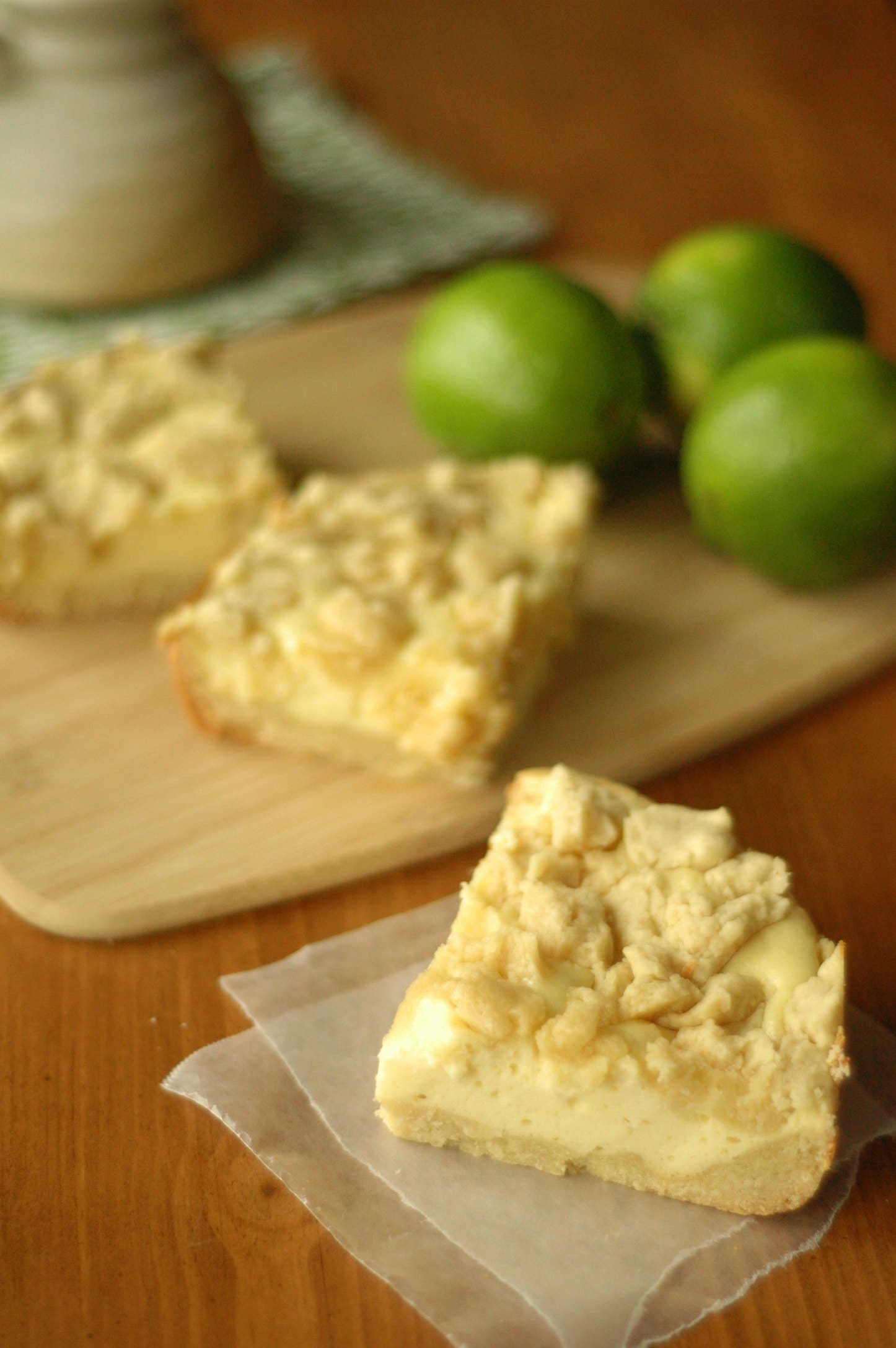 Cheesecake Cookie Bar on wax paper with two bars and three limes on cutting board in background