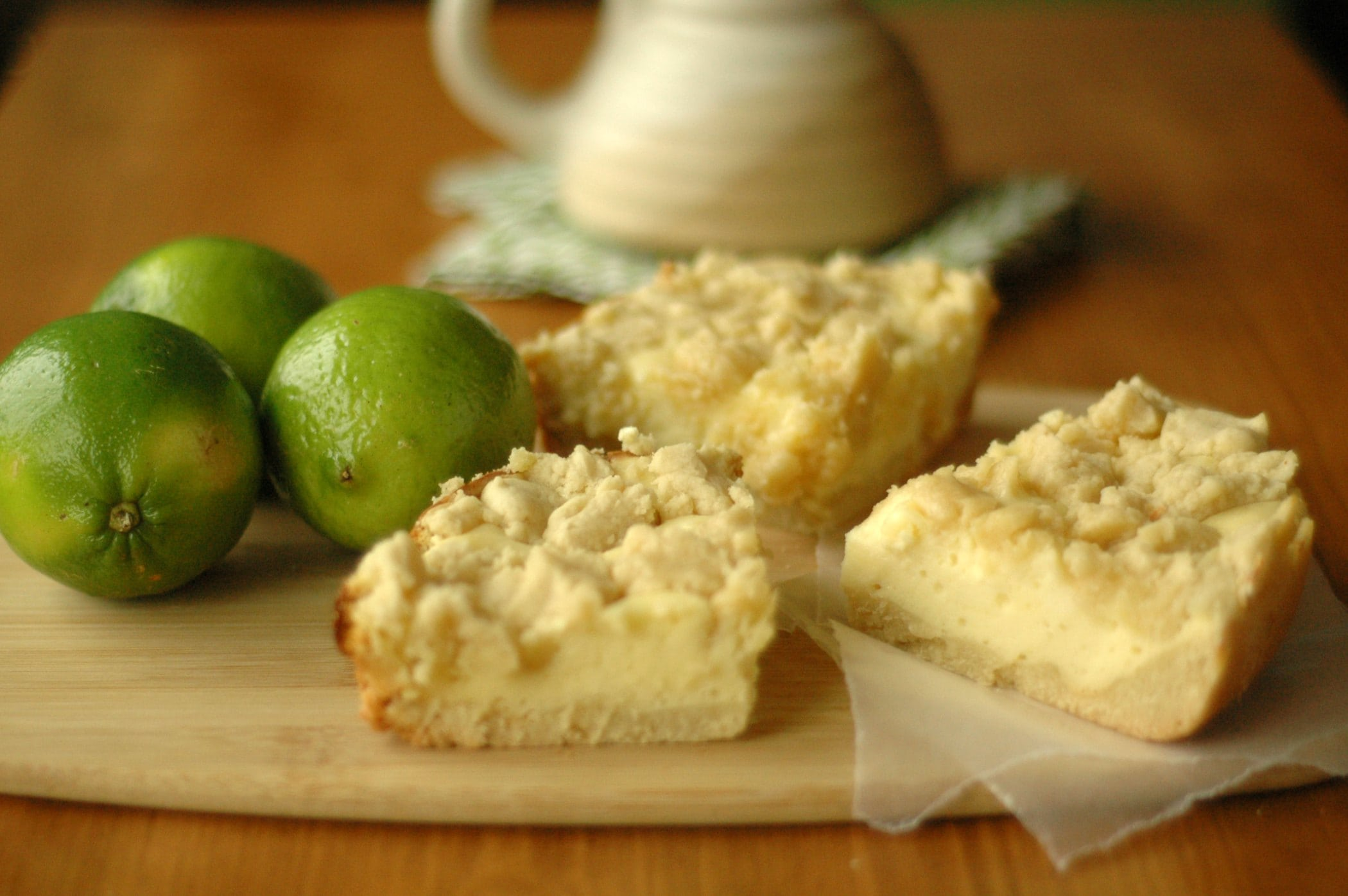 Cheesecake Cookie Bars on cutting board with three whole limes