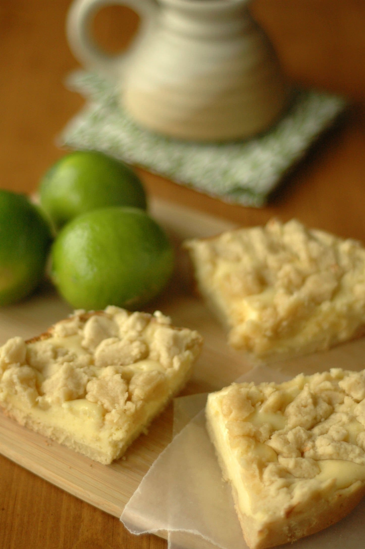 Three cheesecake cookie bars on cutting board with limes