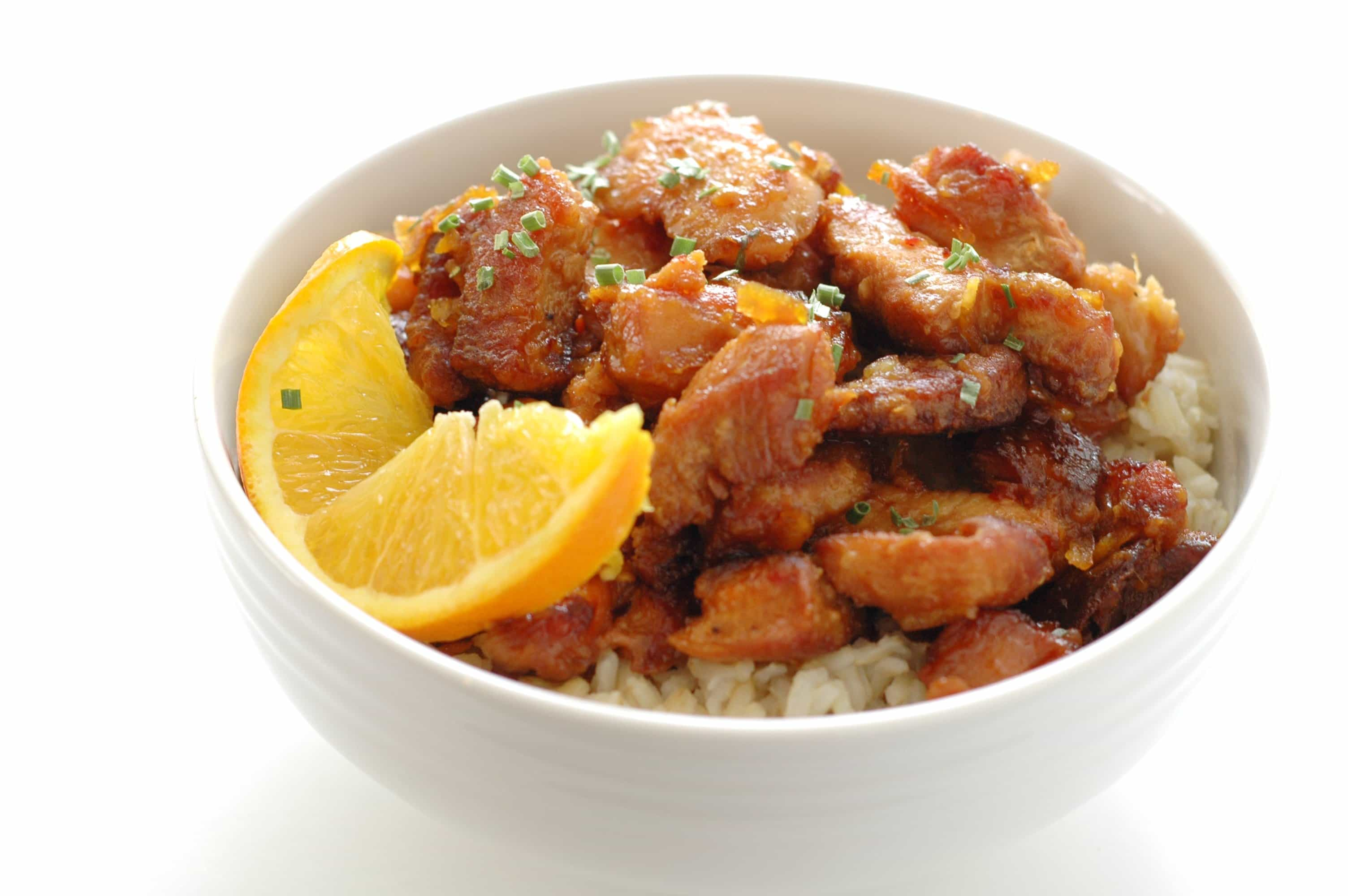 side view of white bowl with orange chicken on bed of rice with slice of orange