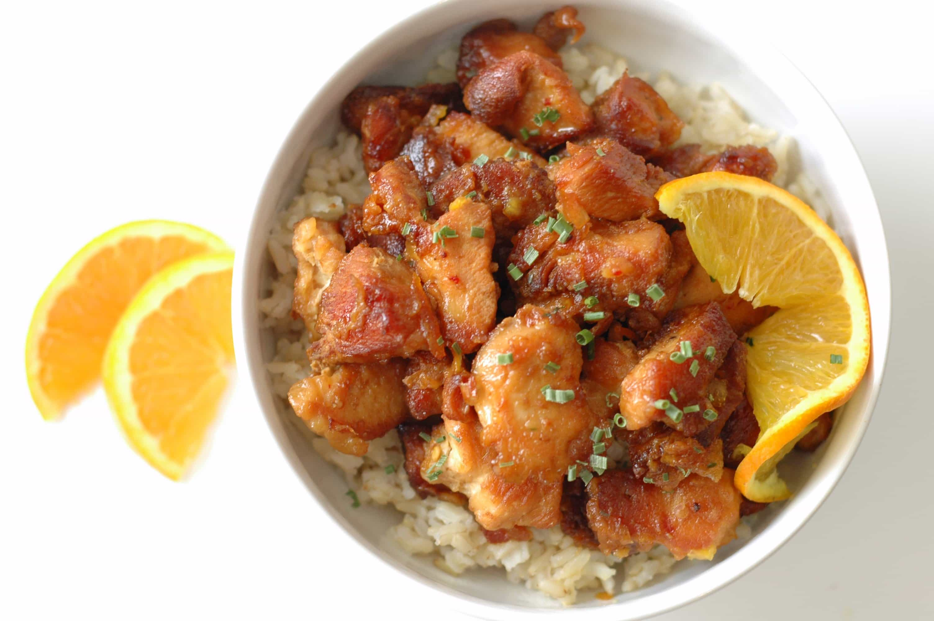 closeup of orange chicken on bed of rice with slice of orange in white bowl