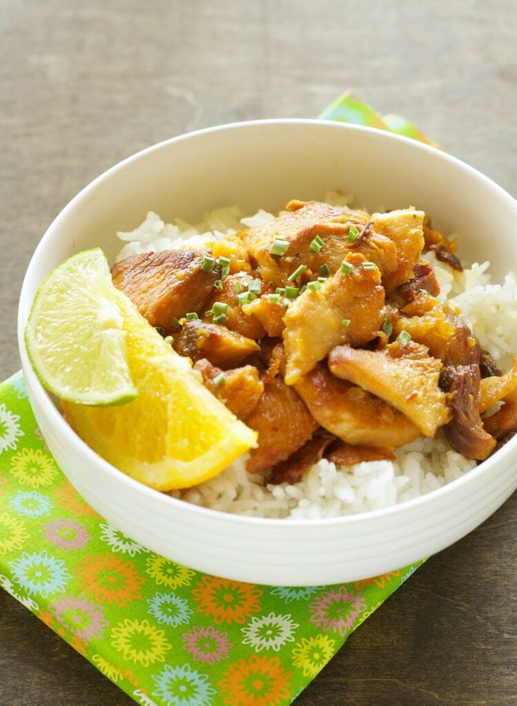 Slow Cooker Honey Crispy Chicken with white rice and lemon/lime wedges in white bowl