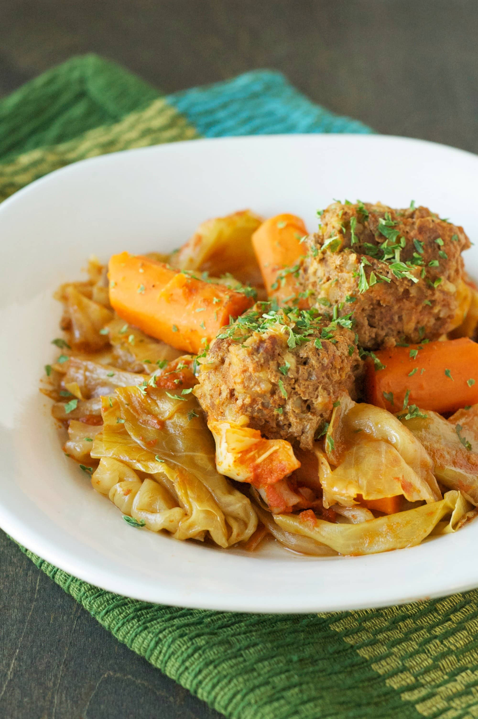 meatballs, carrots and cabbage in white serving plate on blue and green placemat