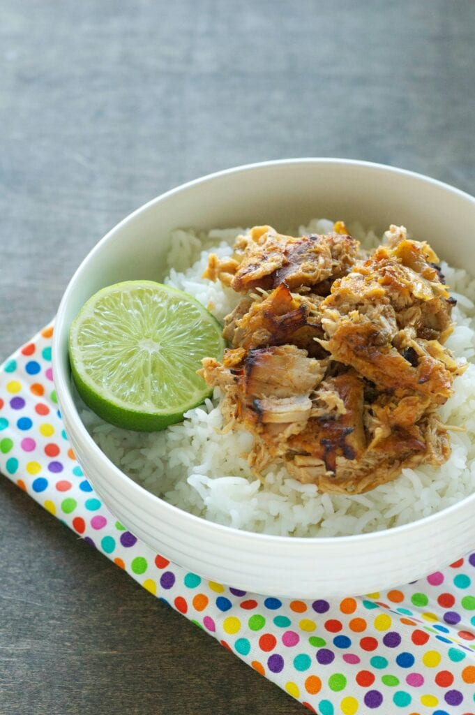 Slow Cooker Crispy Garlic Citrus Carnitas in white bowl with lime wedge