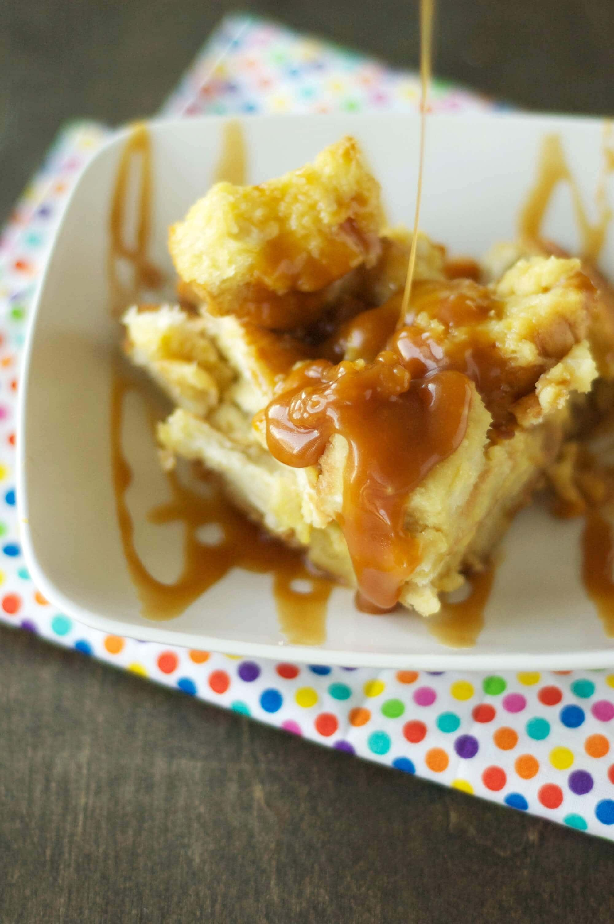 bread pudding being drizzled with salted caramel sauce in white bowl on polka dot napkin