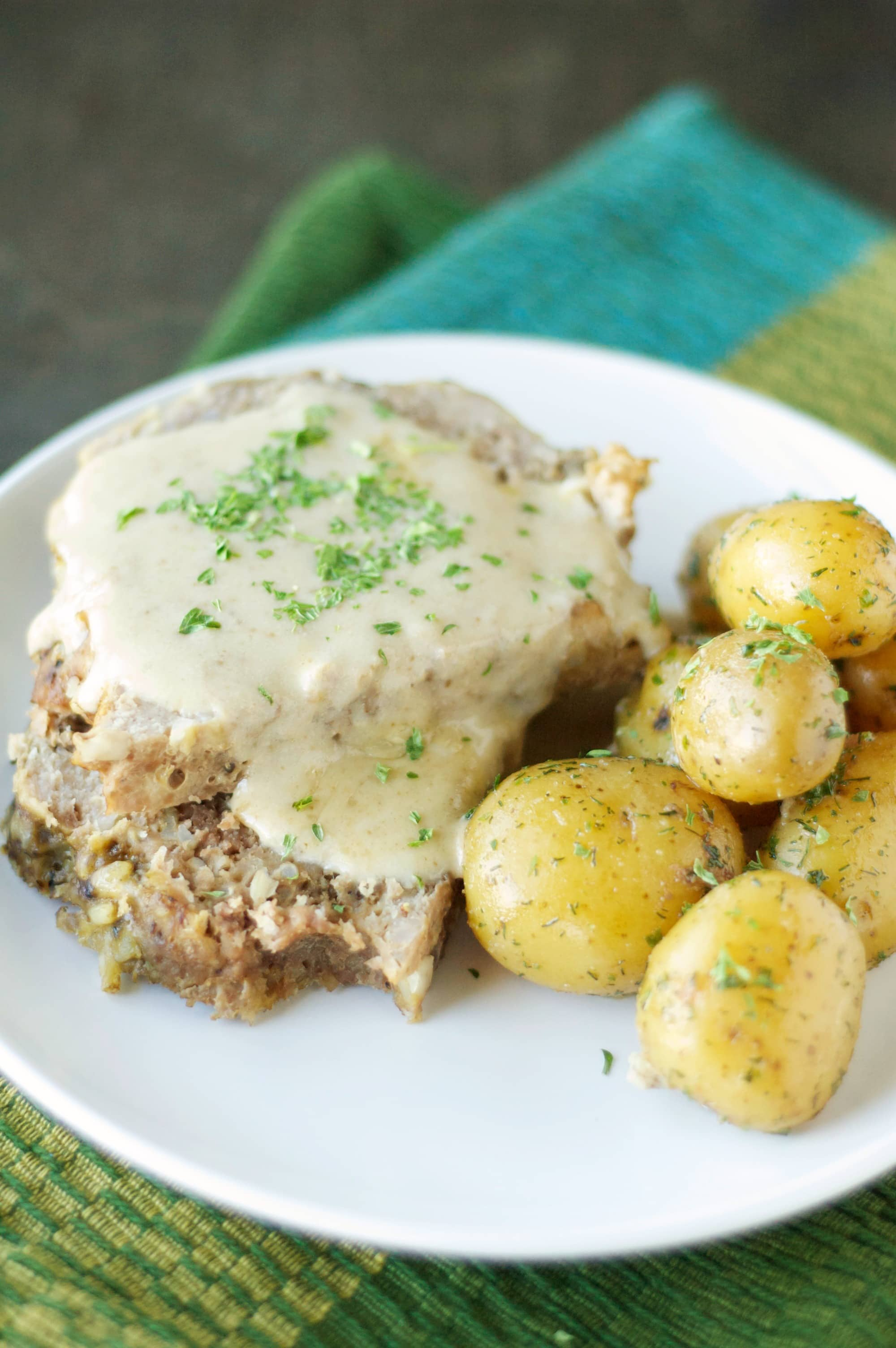 Side view of Slow Cooker Creamy Meatloaf with Baby Dill Potatoes on white plate