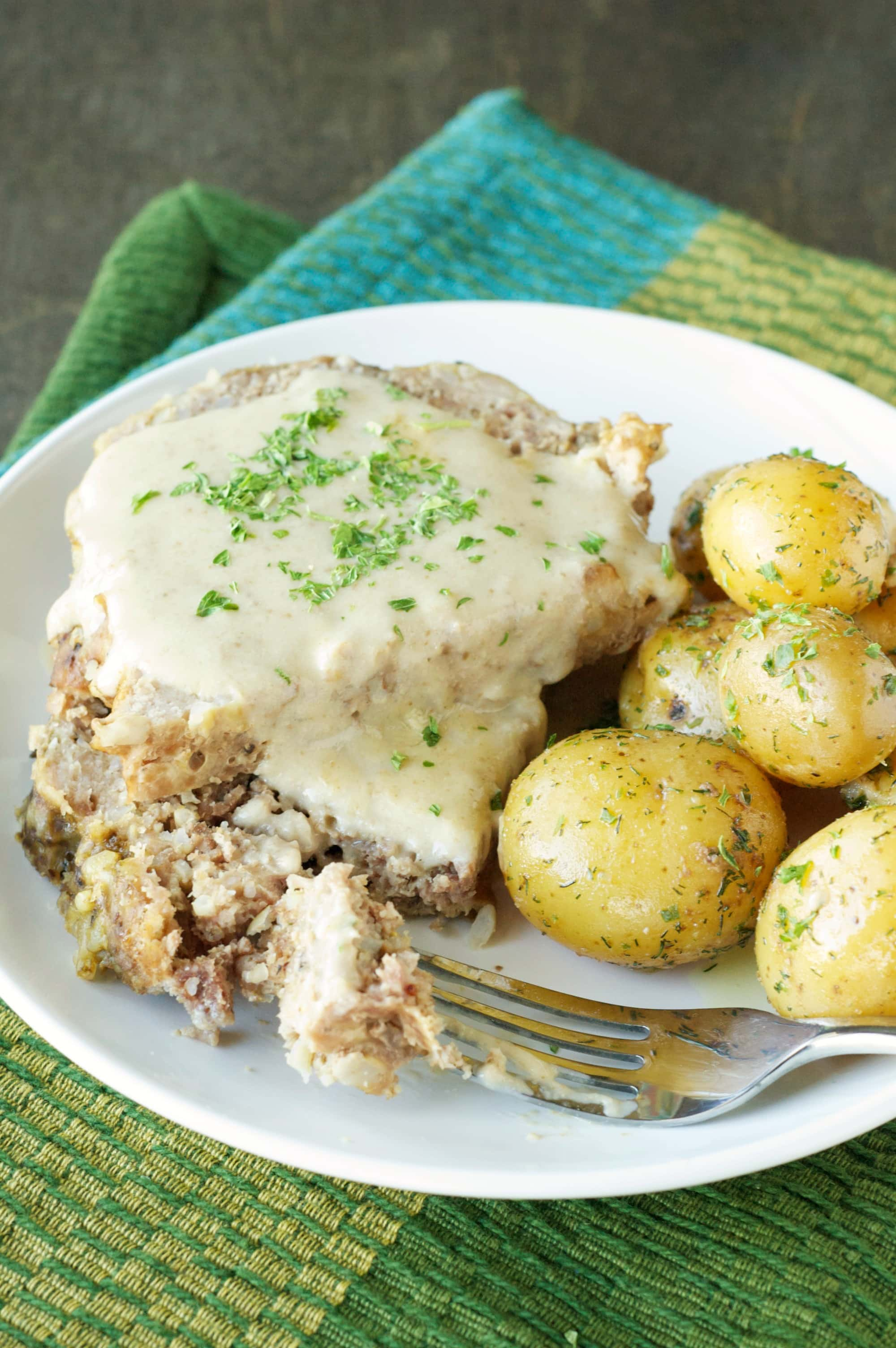 Top view of Slow Cooker Creamy Meatloaf with Baby Dill Potatoes on white plate with fork