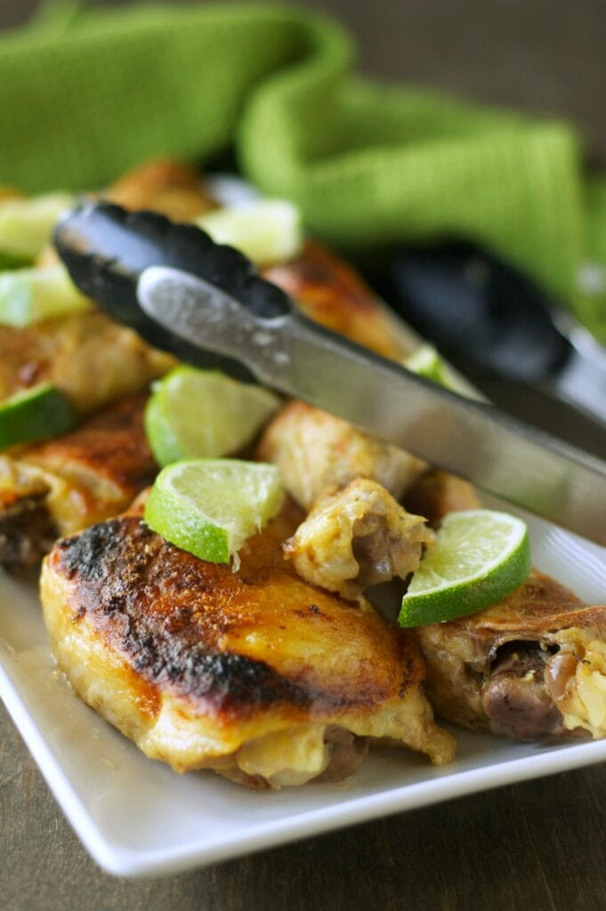Slow Cooker Coconut Lime Chicken on white plate with tongs and lime slices
