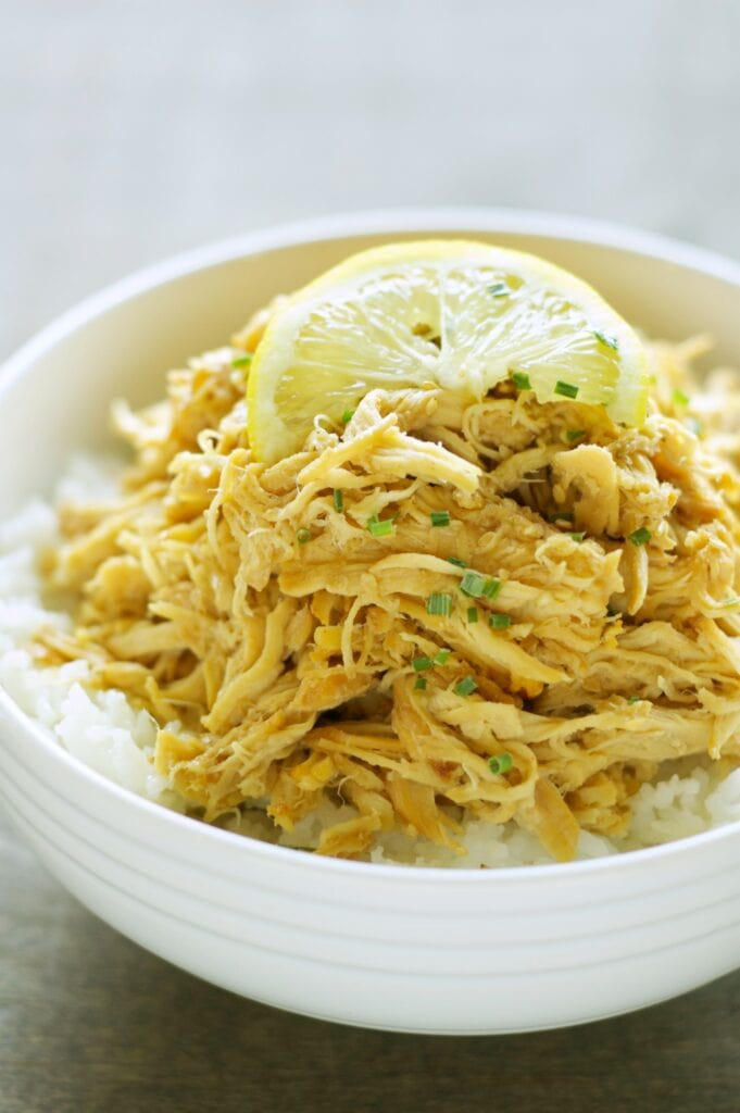 Slow Cooker Lemon Chicken in white bowl with white rice and lemon slice on top