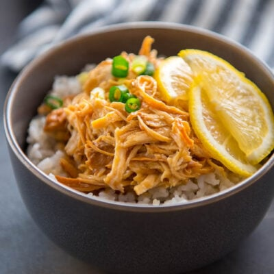 Slow Cooker Lemon Chicken in with lemon slices in gray bowl with rice
