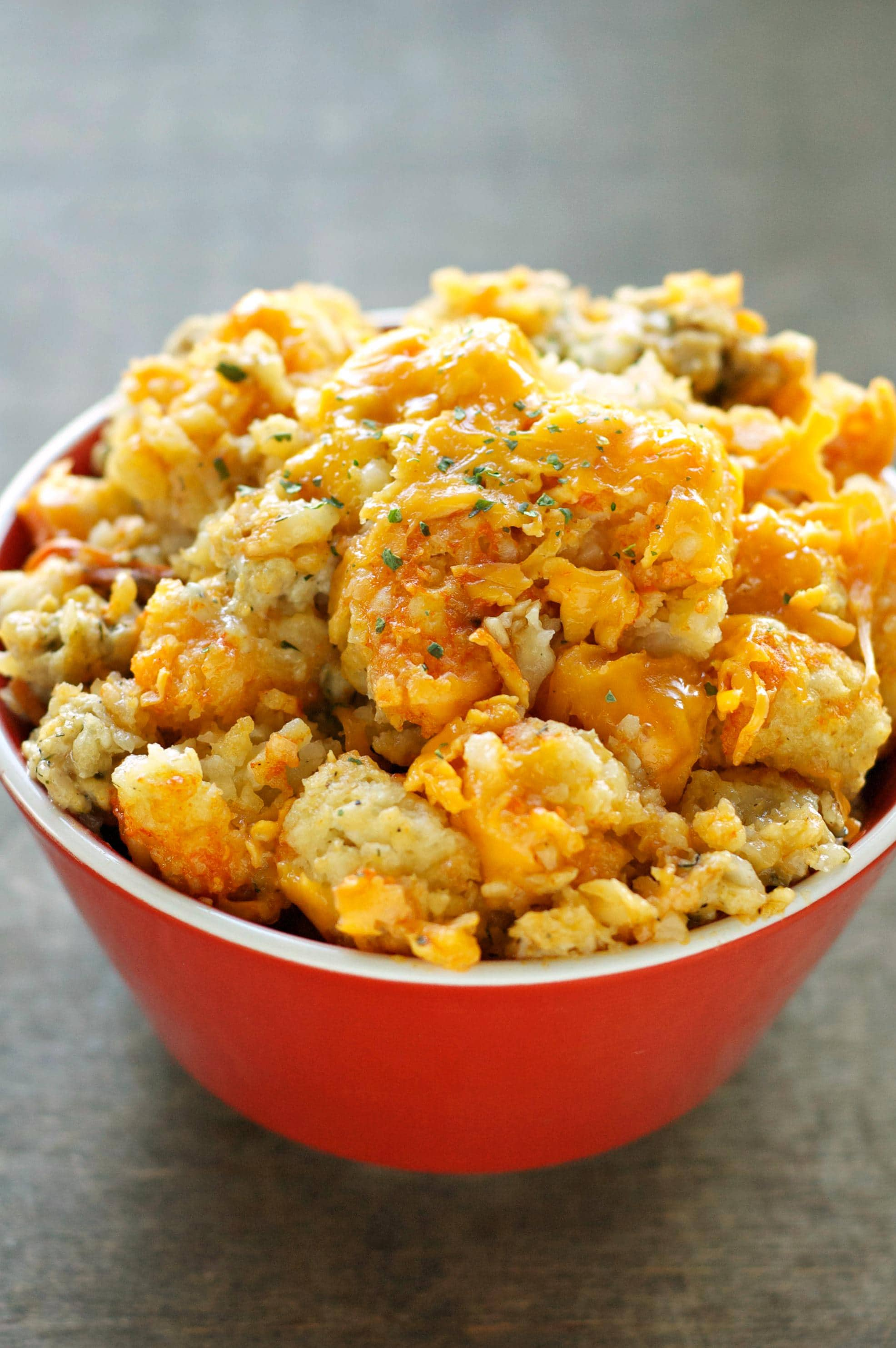 Slow Cooker Buffalo Chicken Tater Tot Casserole covered in melted cheese and sprinkled with seasoning in a red bowl.