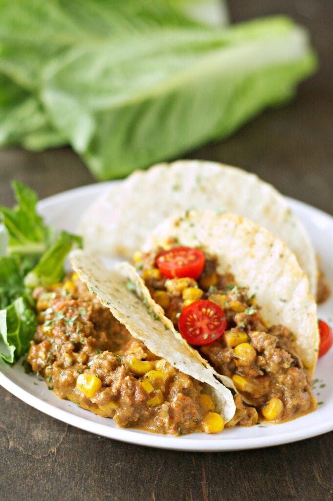 Slow Cooker Cheesy Beefy Tacos on white plate with lettuce in background
