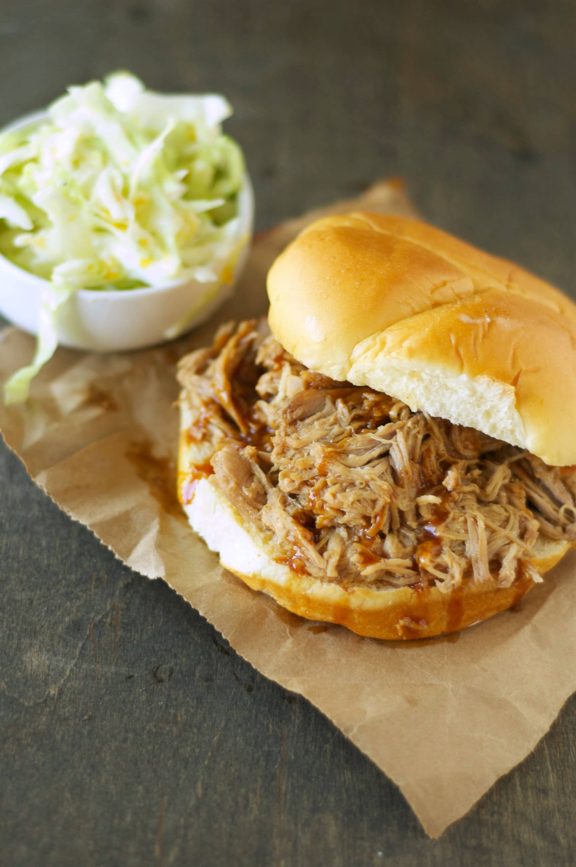 Slow Cooker Pulled Pork on bun with bowl of slaw