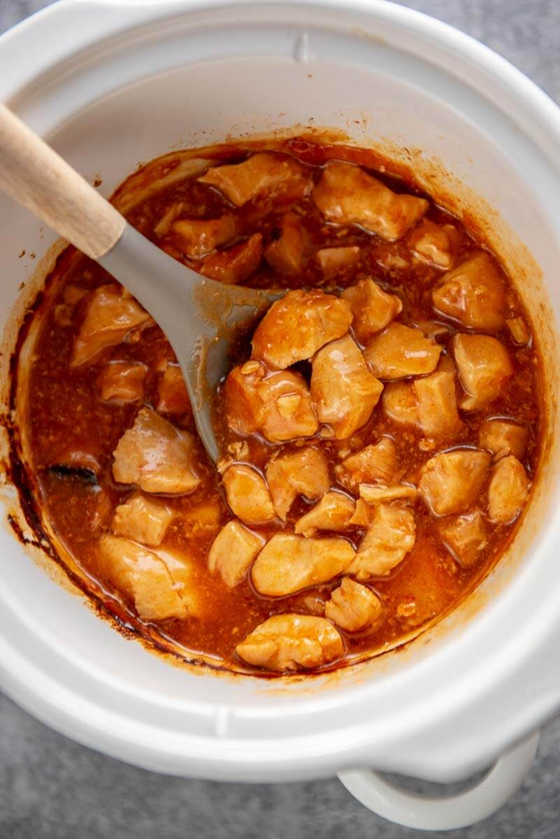 white slow cooker with honey sriracha chicken
