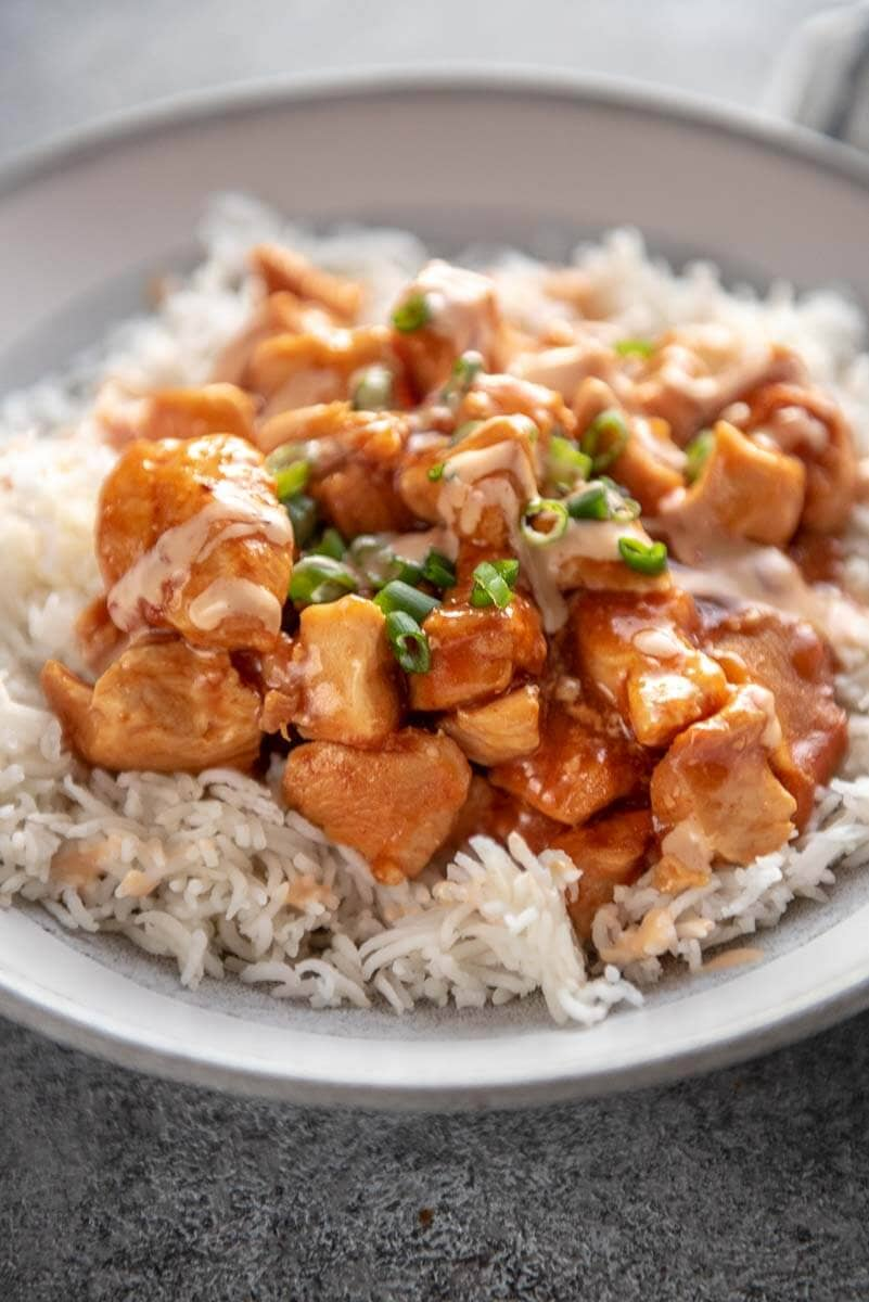 honey sriracha chicken with drizzle and cilantro in white and gray bowl