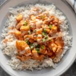 rice topped with honey sriracha chicken in bowl