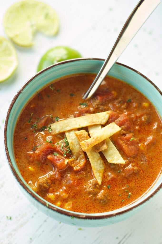 Slow Cooker Beef Enchilada Soup in green bowl with lime slices