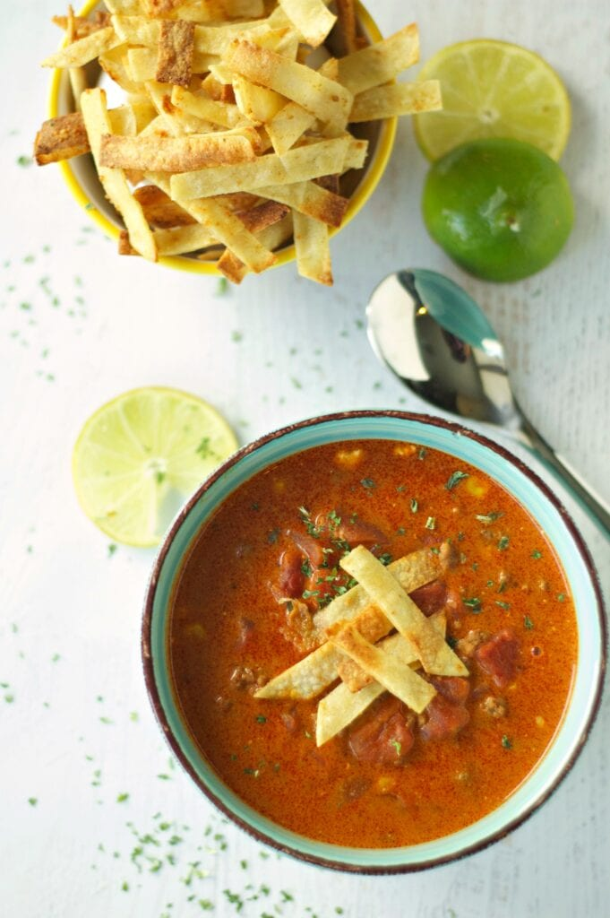 Slow Cooker Beef Enchilada Soup in green bowl with bowl of tortilla strips, lime slices and spoon