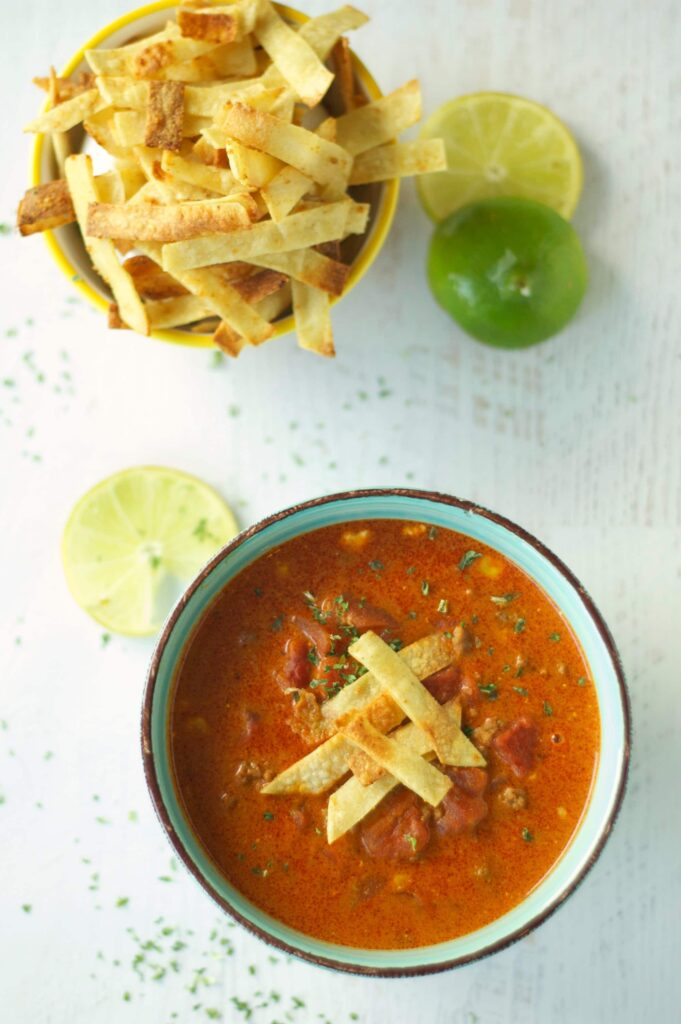 Slow Cooker Beef Enchilada Soup in green bowl with tortilla strips and lime slices