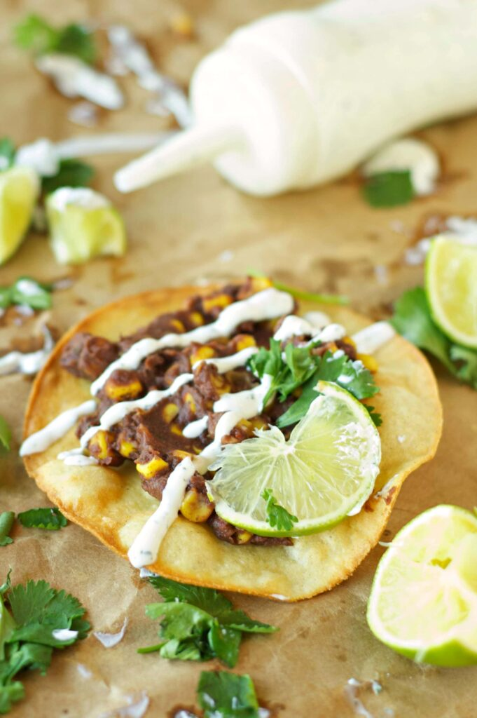 Slow Cooker Black Bean, Corn and Basil Tostadas on wax paper with sour cream drizzle