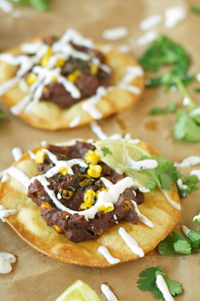 Two Slow Cooker Black Bean, Corn and Basil Tostadas on wax paper with sour cream drizzle