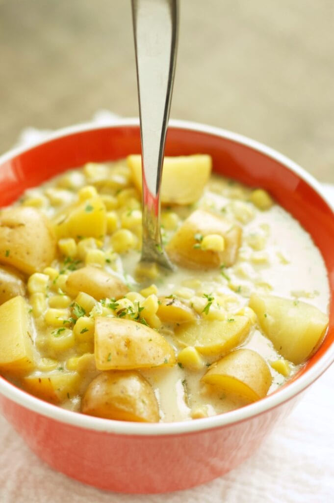 Slow Cooker Corn and Potato Chowder in red bowl with spoon