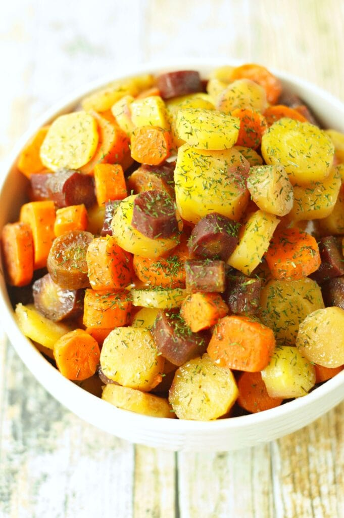 Slow Cooker Carrots with Honey Butter Sauce in white bowl with dill sprinkle