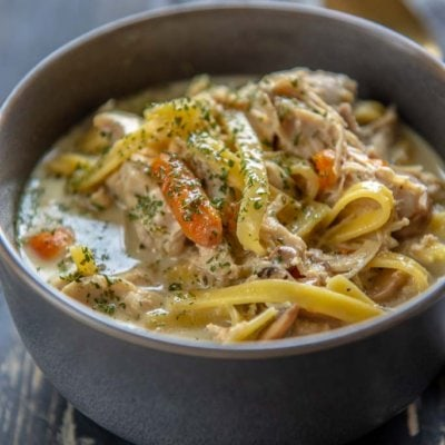 Slow Cooker Creamy Chicken Noodle Soup in a gray bowl topped with parsley