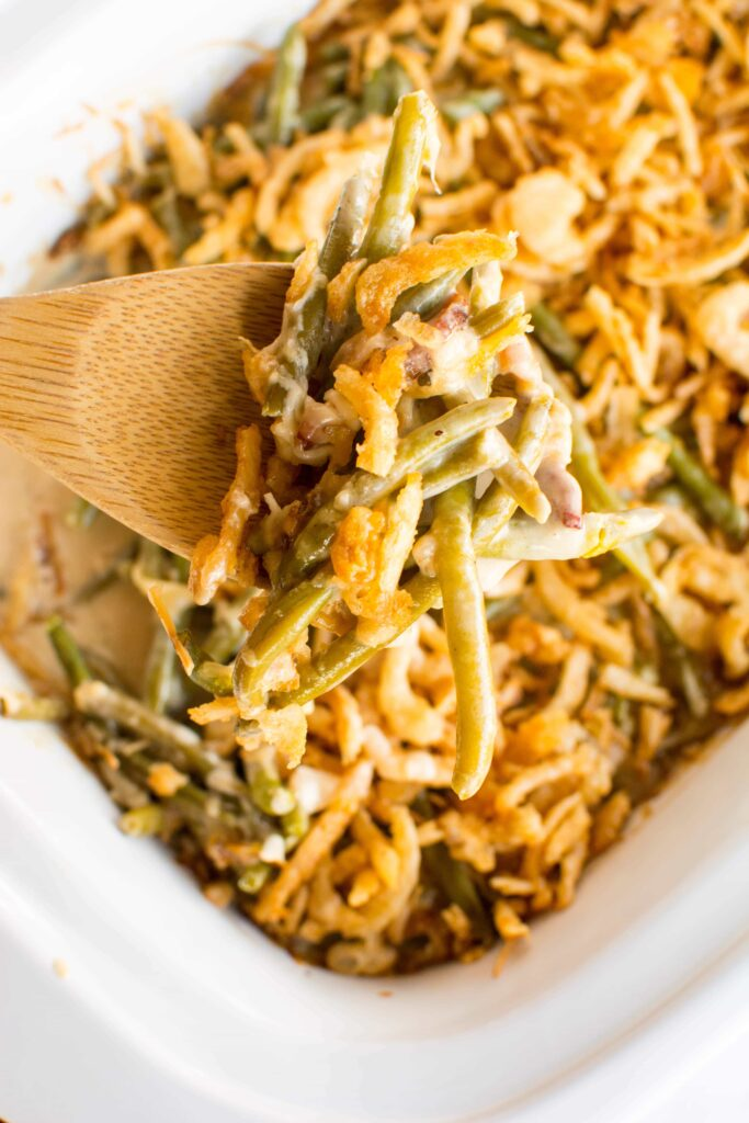 Overhead view of Slow Cooker Fresh Green Bean Casserole on a spoon over a white casserole dish.