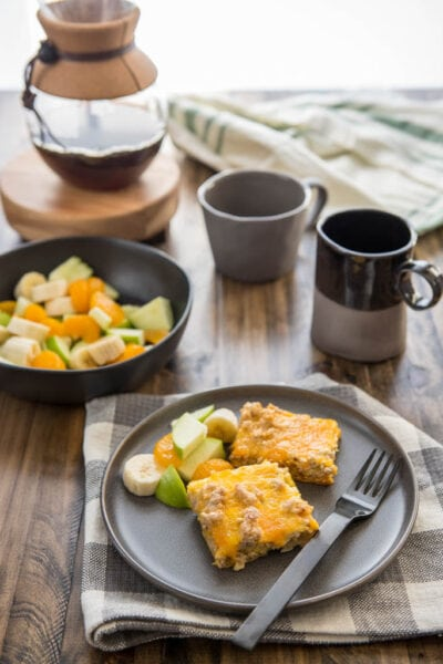 Slow Cooker Easy Breakfast Casserole served on a black plate wtih coffee and fruit.