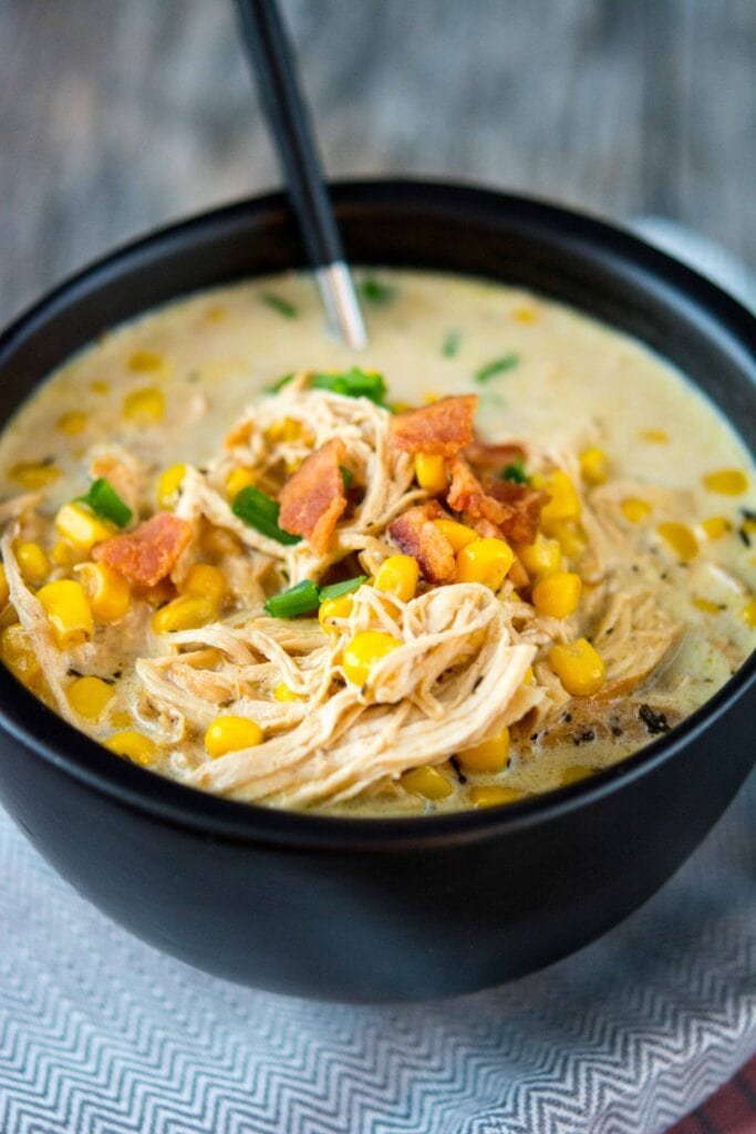 Slow Cooker Chicken Corn Chowder in a black bowl with a black spoon topped with bacon.