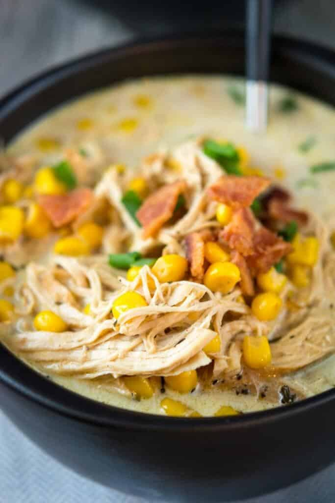 Close up shot of Slow Cooker Chicken Corn Chowder in a black bowl and a black spoon.