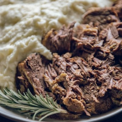 Slow Cooker Roast Beef with mashed potatoes in a white bowl with a sprig of rosemary
