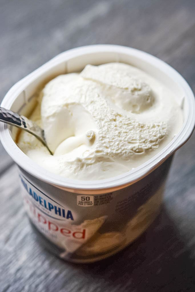 Open tub of whipped cream cheese - Slow Cooker Enchilada Soup