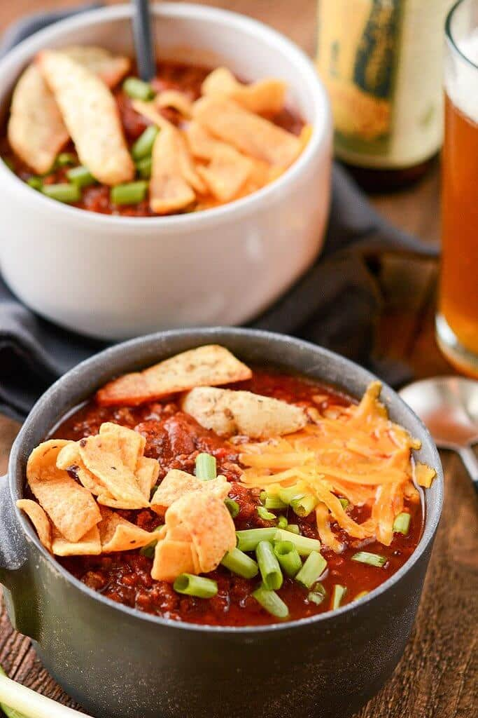 Slow Cooker Tailgate Chili in a metal bowl served with a cold beer