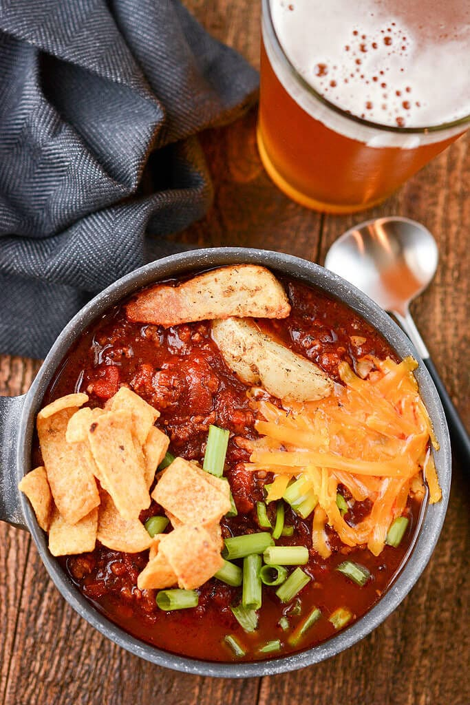 Slow Cooker Tailgate Chili in a bowl with chili topping and a beer