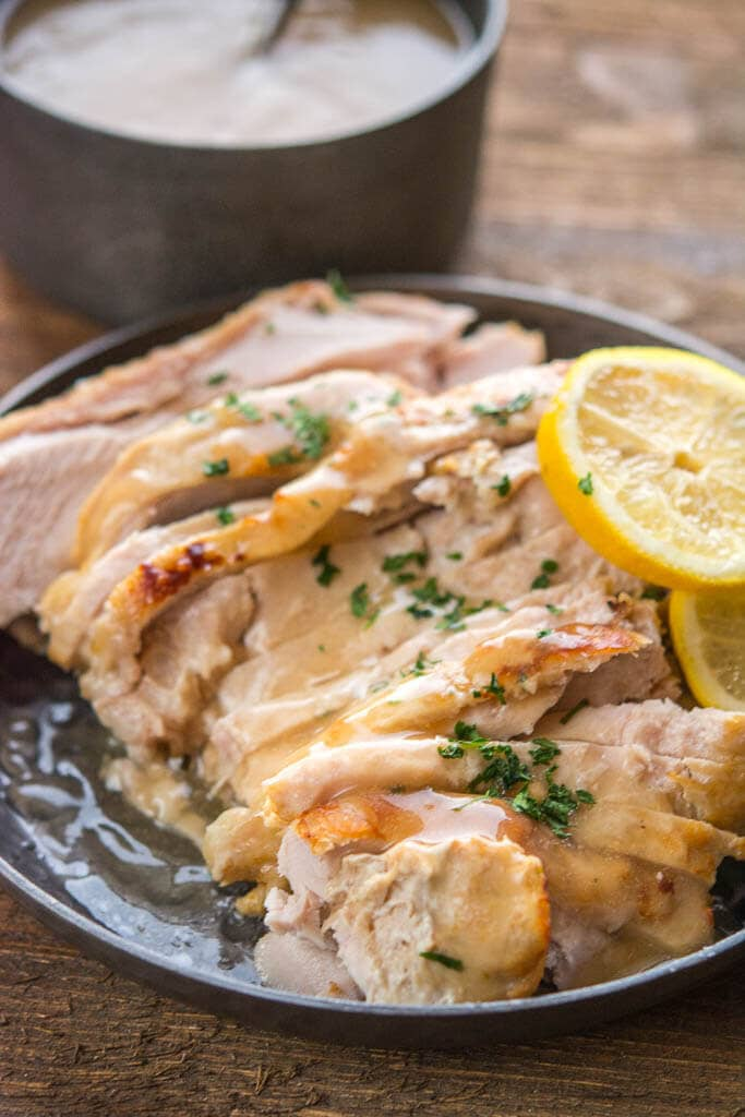 Sliced Slow Cooker Turkey Breast with Gravy on a black plate with lemons and gravy in the foreground