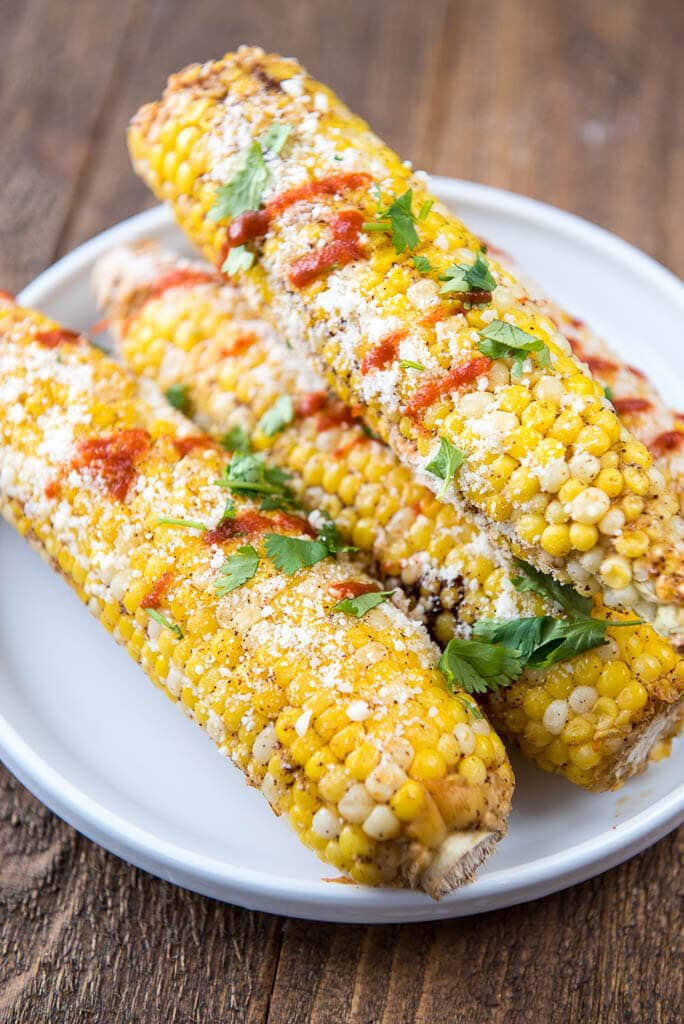 This simple Mexican Corn on the Cob with Sriracha and Cilantro Lime Butter is the perfect simple side dish to go with all your favorite Food Truck Friday main dish creations!