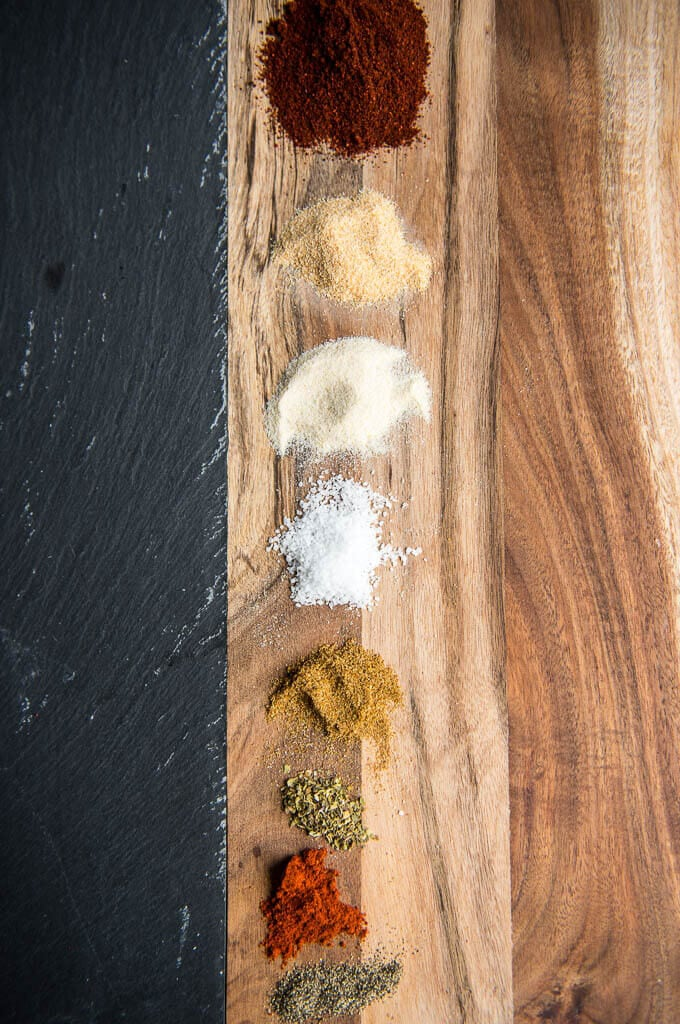 Spices laid out in piles on a cutting board. Spices are used to make this homemade taco seasoning.