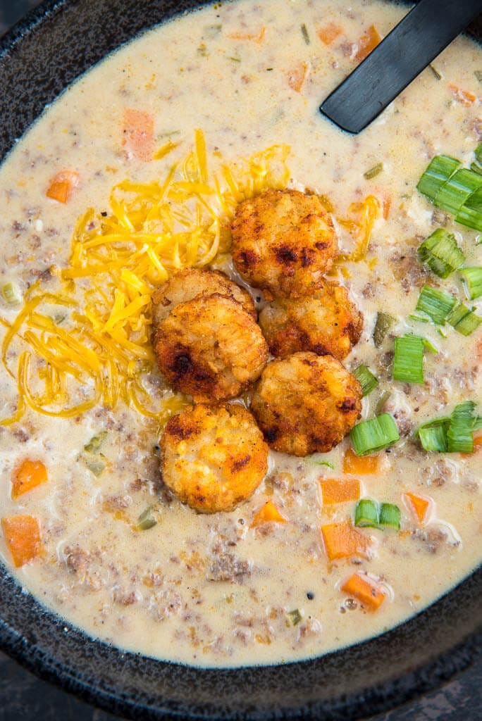 Slow Cooker Cheeseburger Soup topped with tater tot crowns, cheese and scallions in a black bowl with a black spoon.