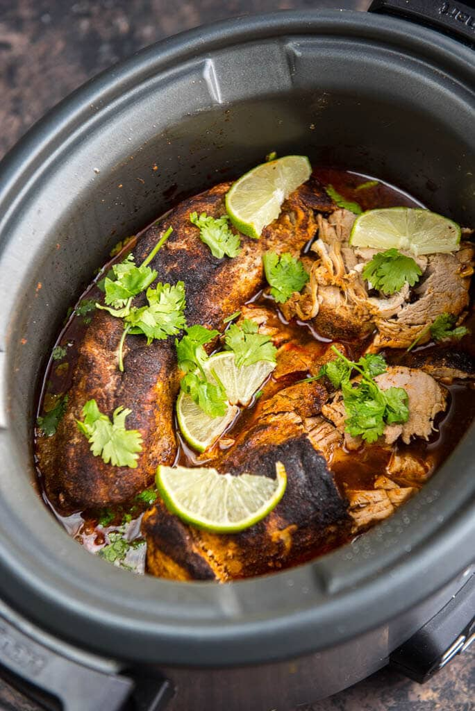 Cooked pork loin with lime and cilantro garnish in slow cooker for Pork loin with seasoning rub for Slow Cooker Chili Lime Pork Roast dinner